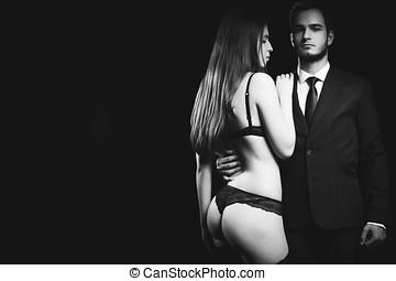 Erotic concept of woman in underwear next to men in suit....