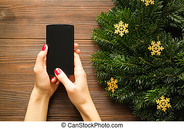 Female hands with red manicure holding a mobile phone with a touch screen on the background of Christmas decorations