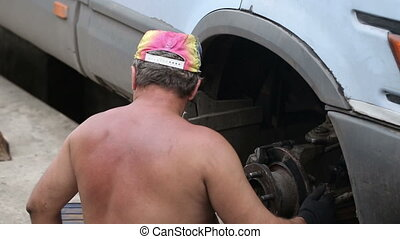 Rural Man Repairing a Car - rural man repairing a car in the...