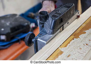 Carpenter using electric plane - Carpenter working with...