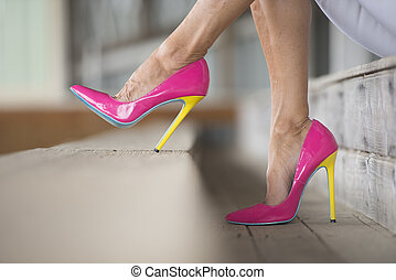 Legs and high heel shoes sitting relaxed