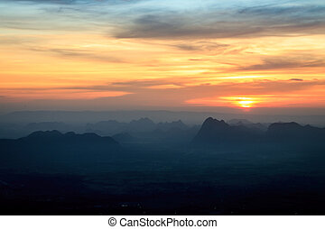 Sunset landscape orange sky and silhouette mountain with fog at Phu Kradueng National Park,Thailand