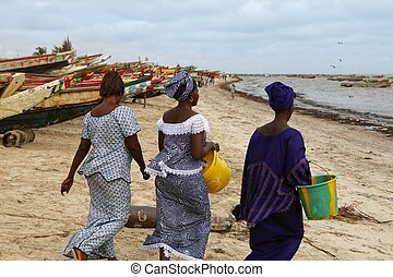 Three women walking beach in Africa Senegal ethnic costumes