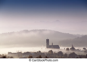 Foggy morning in small town Church in a mist Poland...