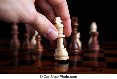 chess game king move - player's hand holding the figure of...