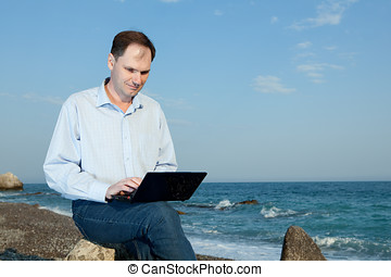 Men with laptop on the beach