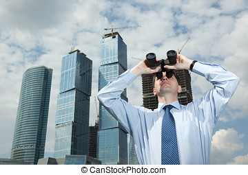 Businessman with binoculars against modern buildings
