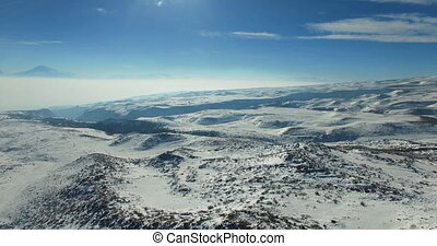 AERIAL: Snowy landscape, flying over the mountain