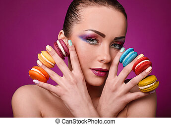 Beauty glamor fashion model girl with colourful makeup and macaroons.