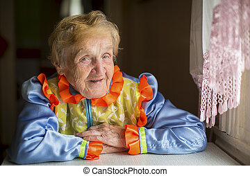 An elderly woman in bright colour Slavic ethnic costume.
