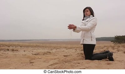 woman girl kneels and throws sand autumn nature cold