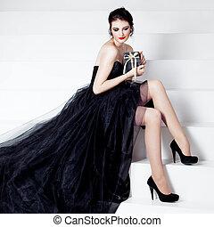 Beauty Brunette model woman holds gift box Elegant girl in a...
