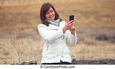 woman girl smartphone makes self phone sitting on a dry tree...