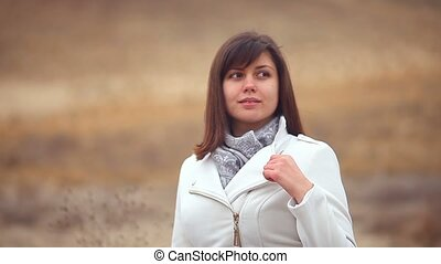 girl woman in autumn coat on nature of the wind is blowing brown background