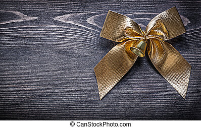 Goldish bow on wooden board holiday concept