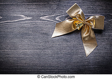 Goldish bow with bell on wooden board holiday concept