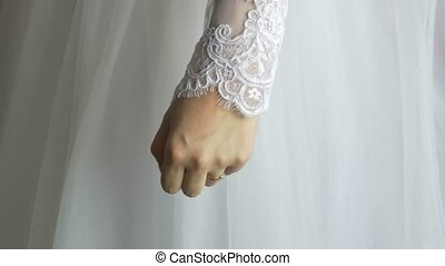 Hand of the bride on a background of dress of the bride wedding item charges