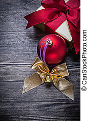 Set of shining bauble bow gift box on wooden board
