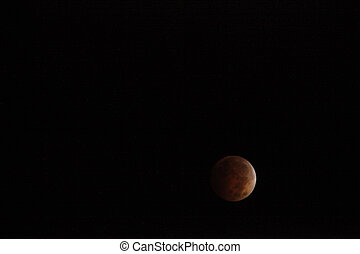 Lunar Eclipse - The Earths shadow shrouds the full moon in...