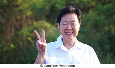 Asian senior woman thumb up and smiling with green nature...