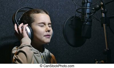 teen girl in headphones singing into a microphone recording...
