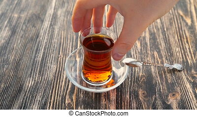 Pouring tea into a cup on a wooden table