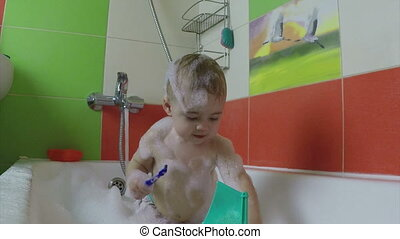cute one year old girl taking a relaxing bath with foam -...