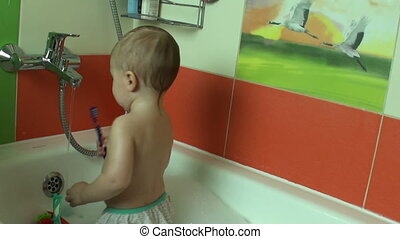 little baby one year of age in the bathroom brushing her...