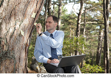 Businessman working with laptop outdoors - Businessman...