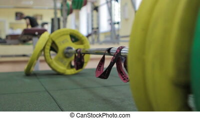 Closeup barbell, athlete puts the barbell plates to the bar...