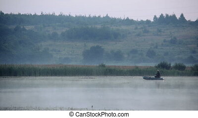Fisherman on an inflatable boat in the early morning fishing...