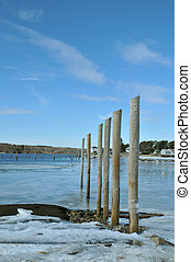 Pilings and Ice - Pilings standing up in ice filled water in...