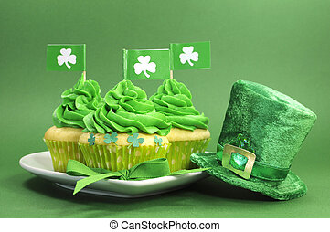 Happy St Patricks Day green cupcakes with shamrock flags and leprechaun hat against a green background