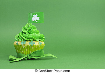 Happy St Patricks Day green cupcake with shamrock flag on green background with copy space for your text here.