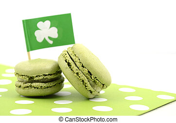 Happy St Patricks Day green macaron cookies with shamrock flag on white table.