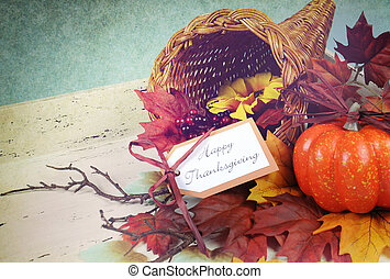 Happy Thanksgiving cornucopia with Autumn Fall leaves, pumpkin, sunflower and berries on white shabby chic tray against a pale blue background, with retro grunge filter.
