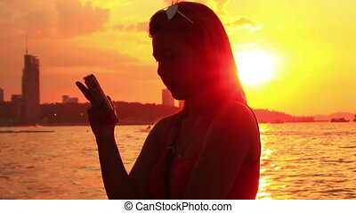 young woman with smartphone at beach at sunset