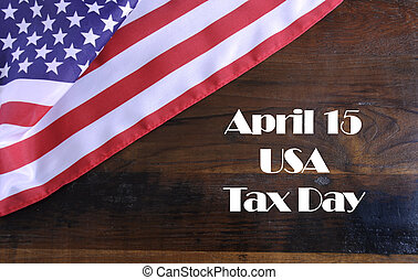 April 15, USA Tax Day reminder on dark recycled wood...