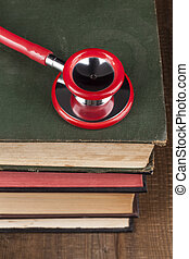 Red Stethoscope on Books Pile - Red Stethoscope Closeup on...