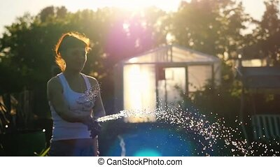 Summer gardener smiling woman watering watering flowers and...