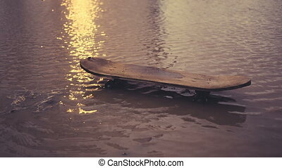 Old skateboard in a dirty puddle. Close up video.