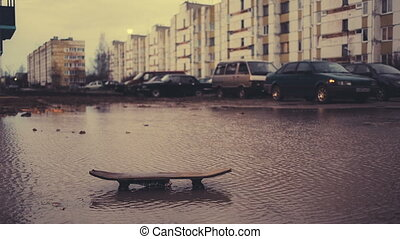Old skateboard in a dirty puddle on a multi storey building...