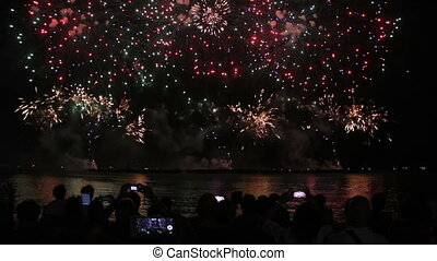 people with smartphones watching fireworks