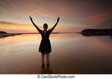 Woman outstretched arms praising perfect day success - A...