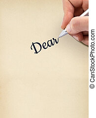 Hand writing quot;Dearquot; on aged sheet of paper - Hand...