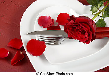 Romantic Valentines Day table place setting with white heart shape plates with rose and petals on red wood background.