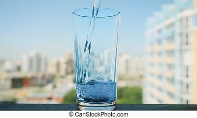 Pouring water in glass with pill in slowmotion. Aspirin...
