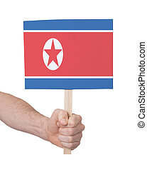 Hand holding small card - Flag of North Korea - Hand holding...