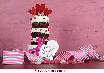 Novelty triple layer red velvet cupcake on white cake stand with ribbons and candy against a vintage shabby chic pink and red wood background, with Happy Valentines Day greeting gift tag and sample text.