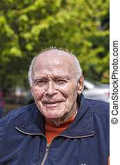 smiling happy senior man sitting in his garden - portrait of...
